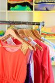 разнообразие одежды на деревянные вешалки на фоне полки — Стоковое фото