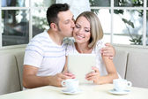 Young couple taking photo with tablet at home — Stock Photo