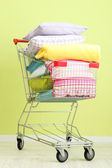 Shopping cart with pillows, on green wall background — Stock Photo