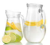 Cold water with lime, lemon and ice in pitchers isolated on white — Stock Photo