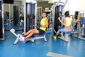 Guy and girl engaged in simulator at gym — Стоковое фото
