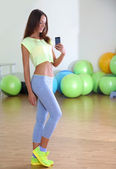 Pretty sporty girl photographing herself in mirror at phone in fitness room — ストック写真