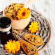 Medicine bottle and calendula flowers on wooden background — Stock Photo #30564729