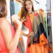 Beautiful girl trying dress near mirror on room background — Stock Photo #30566079
