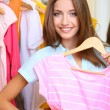 Beautiful girl chooses clothes on room background — Stock Photo #30566085