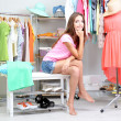 Beautiful girl thinking what to dress in walk-in closet — Stock Photo #30566087
