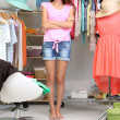 Beautiful girl thinking what to dress in walk-in closet — Stock Photo #30566091