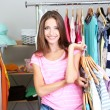 Beautiful girl with lots clothes in room background — Stock Photo #30566105