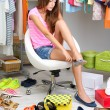 Beautiful girl chooses shoes in room — Stock Photo #30566107