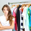 Beautiful young stylist near rack with hangers — Stock Photo #30566109