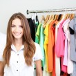 Beautiful young stylist near rack with hangers — Stock Photo #30566111
