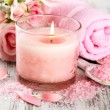 Beautiful spa setting with pink candle and flowers on wooden background — Stock Photo