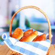 Fresh baked pasties in wicker basket, on bright background — Stock Photo