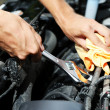 Hand with wrench. Auto mechanic in car repair — Stock Photo #30567899