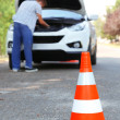 Stock Photo: Broken down car with warning cone