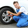 Auto mechanic changing wheel — Stock Photo #30567937