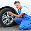 Auto mechanic changing wheel — Stock Photo