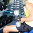 Guy with dumbbells on gym background close-up — Stock Photo #30568091