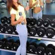 Pretty sporty girl with dumbbells in gum — Stok fotoğraf