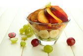 Beyaz ahşap masa üzerinde cam kase lezzetli meyve salatası — Stok fotoğraf