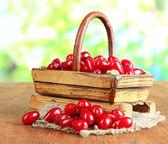 Fresh cornel berries in basket on wooden table — Stock Photo
