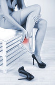 Girl with sore foot in shades of grey — Stock Photo