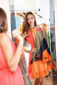 Vacker flicka försöker klä nära spegeln på rummet bakgrund — Stockfoto