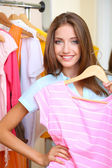 Beautiful girl chooses clothes on room background — Foto de Stock