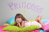 Little girl lying on bed in room on grey wall background — Stock Photo