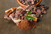 Cocoa beans in bowl, cocoa powder and spices on wooden background — Stock Photo