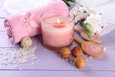 Beautiful spa setting with pink candle and flowers on purple wooden background — Stock Photo