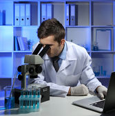 Unga laboratorium forskare tittar på mikroskopet i lab — Stockfoto