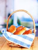 Frais pâtés cuits au four dans le panier d'osier, sur fond clair — Photo