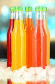 Botellas con deliciosas bebidas con cubitos de hielo, sobre fondo brillante — Foto de Stock