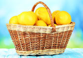 Ripe lemons in wicker basket on table on bright background — Stock Photo