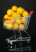 Ripe lemons in trolley isolated on black — Stock Photo
