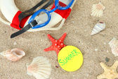 Composition with lifebuoy, goggles on sand background — Stock Photo