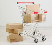 Shopping cart with carton, on gray background — Stock Photo