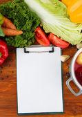 Свежие овощи и специи и бумага для заметок, на фоне деревянных — Стоковое фото