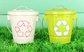 Recycling bins on green grass on color wooden background — Stock Photo