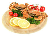 Boiled crabs with lemon slices and tomatoes, on wooden board, isolated on white — Stock Photo