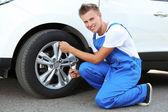 Auto mechanic changing wheel — Stock Photo