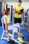 Girl and trainer engaged in simulator in gym — 图库照片