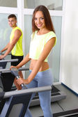 Guy and girl on treadmills at gym — Stock Photo