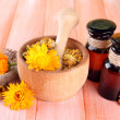Medicine bottles and calendula flowers on wooden background — Stock Photo #30611867