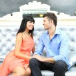 Beautiful young romantic couple sitting on sofa — Стоковая фотография