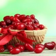 Fresh cornel berries in basket on wooden table — Stock Photo