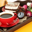 Cup of tea with cakes on wooden tray on table in room — ストック写真
