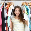 Beautiful young woman near rack with hangers — Stock Photo #30613425