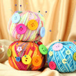 Colorful buttons and multicolor wool balls, on color fabric background — Stock Photo #30616899